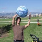 Student throwing Earth-like beach ball